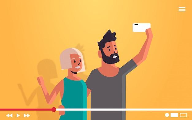 Pareja usando teléfono celular hombre mujer tomando selfie foto en la cámara del teléfono inteligente transmisión de video en vivo retransmitido concepto de redes sociales retrato horizontal