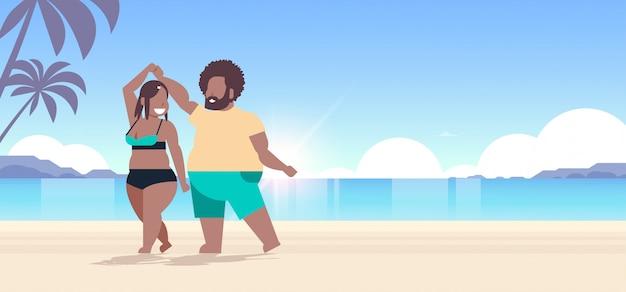 Pareja vistiendo ropa de playa hombre mujer bailando divirtiéndose concepto de vacaciones de verano hermosa