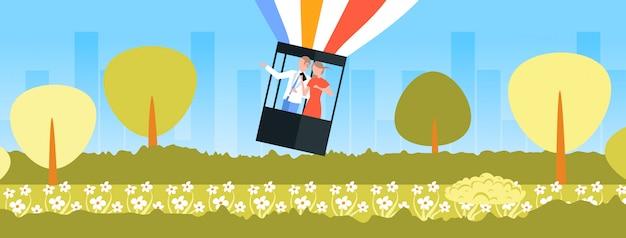 Pareja volando en la canasta de globo aerostático mujer usando teléfono celular hombre señalando con la mano algo romántico fecha exploración concepto verano parque paisaje urbano fondo horizontal