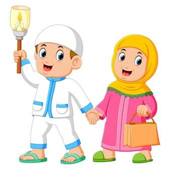 Parejas musulmanas caminando y sosteniendo antorcha.