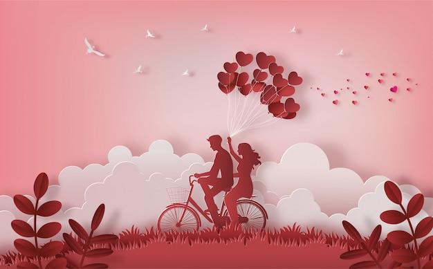 Pares felices que montan a lo largo en la montaña con una mano que sostiene los globos en forma de corazón.