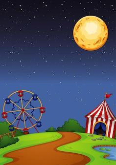 Parque de atracciones con circo en escena nocturna.