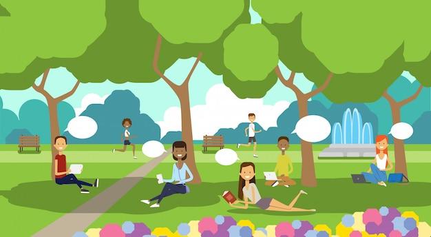 Parque de la ciudad gente relajante burbujas de chat sentado césped verde usando laptop picnic hombre mujer árboles paisaje fondo horizontal plano