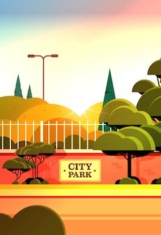 Parque de la ciudad tablero de la muestra en la valla hermoso día de verano puesta de sol paisaje vertical de fondo