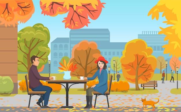 Parque de otoño y pareja bebiendo café cerca de café