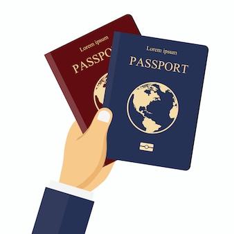 Pasaportes rojos y azules en la mano