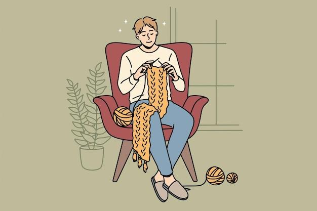 Pasatiempos caseros y concepto de tejer. joven sonriente personaje de dibujos animados sentado en casa en sillón tejer bufanda ilustración vectorial