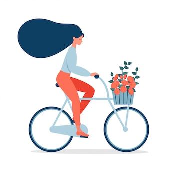 Paseo de la mujer en la bicicleta con el ramo en cesta