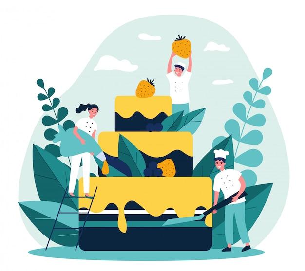 Pasteleros que cocinan gran pastel de cumpleaños