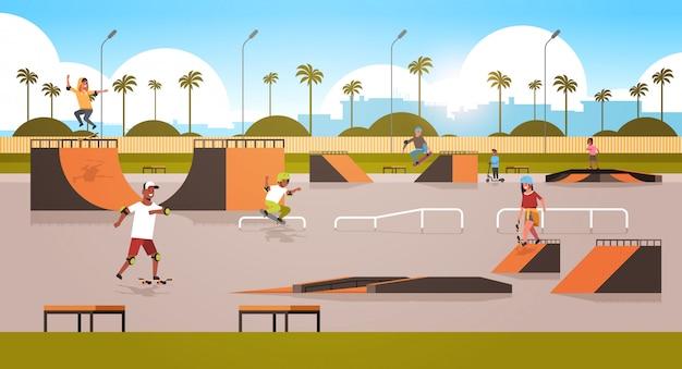 Los patinadores que realizan trucos en el parque público de skateboard con varias rampas para el skateboarding raza mixta adolescentes divirtiéndose montando patinetas paisaje urbano de fondo plano de longitud completa horizontal