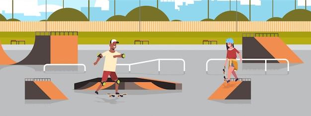 Los patinadores realizan trucos en el parque público de patinetas con varias rampas para el skateboarding raza mixta adolescentes pareja divirtiéndose montando patinetas paisaje fondo plano de cuerpo entero horizontal