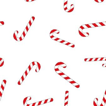 Patrón sin costuras de navidad con dulces sobre fondo blanco.