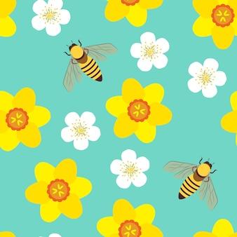 Patrón sin fisuras con abejas, narcisos amarillos y flores blancas sobre fondo azul.