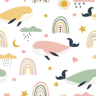 Patrón sin fisuras con ballenas y arco iris en estilo boho.