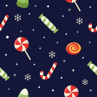 Patrón sin fisuras con dulces de navidad de dibujos animados lindo aislado sobre fondo azul.