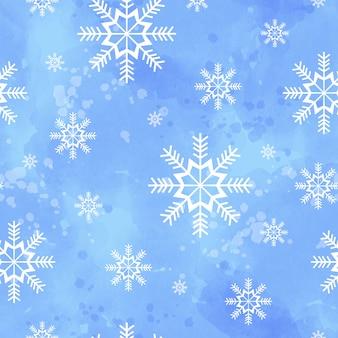Patrón sin fisuras de invierno con copos de nieve sobre un fondo azul acuarela.