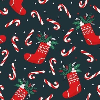 Patrón sin fisuras para navidad con calcetines, follaje, bastones de caramelo y bayas.
