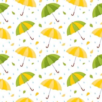 Patrón sin fisuras con paraguas multicolores, gotas de lluvia y hojas caídas.