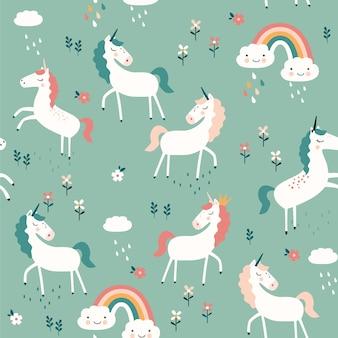 Patrón sin fisuras con unicornios, arco iris y flores sobre fondo azul.