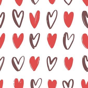 Patrones sin fisuras con corazones dibujados a mano rojo y marrón