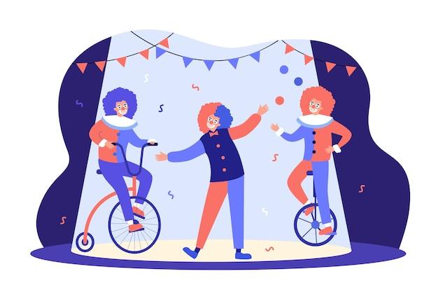 Payasos actuando en la arena del circo, andar en bicicleta, malabarista en equilibrio sobre monociclo.