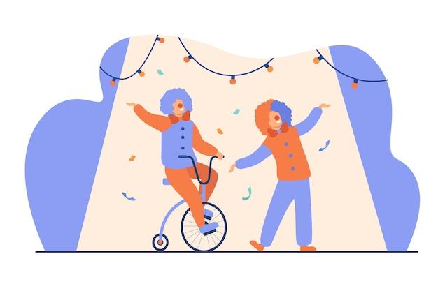 Payasos felices de pie en la ilustración de vector plano de arena de circo. personajes de dibujos animados joker que realizan espectáculo sobre fondo de colores. concepto de comedia y entretenimiento.