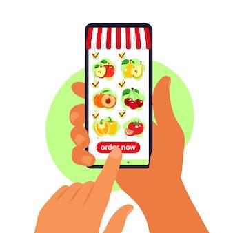 Pedido de comida en línea entrega de comestibles. mano que sostiene el teléfono inteligente con catálogo de productos en la página del navegador web