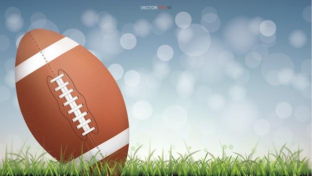 Pelota de fútbol americano o pelota de fútbol de rugby en la cancha de césped verde con luz de fondo bokeh borrosa