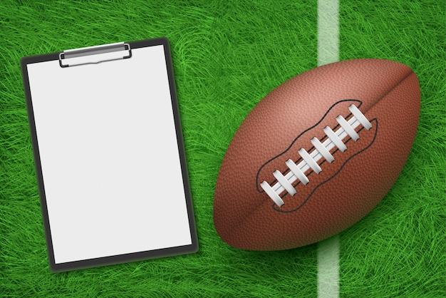 Pelota de rugby y portapapeles tumbado en el estadio de hierba verde vista superior