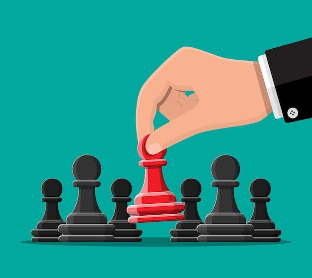 Peón de ajedrez único rojo que se encuentra entre los grises.