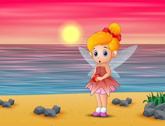 Pequeña hada linda del amor que se coloca en la playa