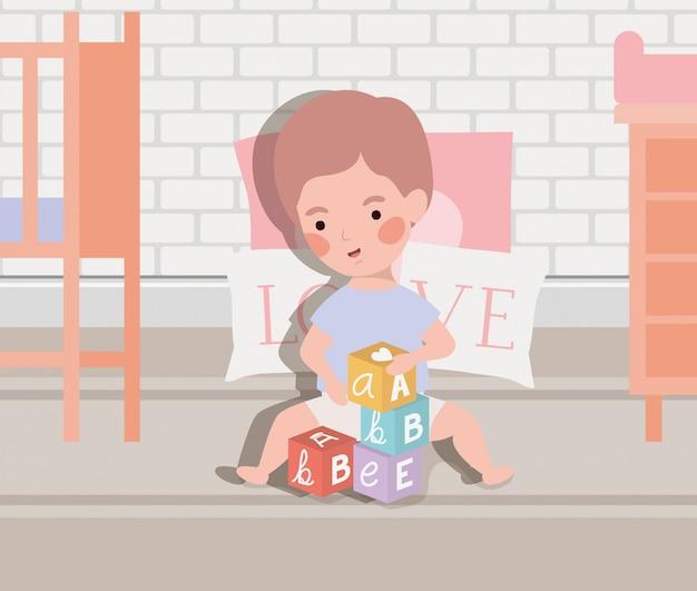 Pequeño bebé que juega con los bloques del alfabeto