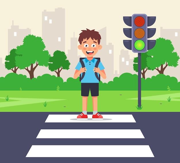 Un pequeño colegial cruza la calle hacia un semáforo en verde en un paso de cebra. ilustración de personaje plano.