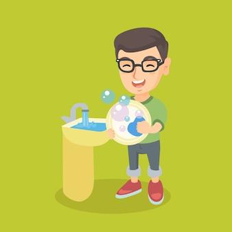 Pequeño muchacho caucásico lavando platos en el fregadero.