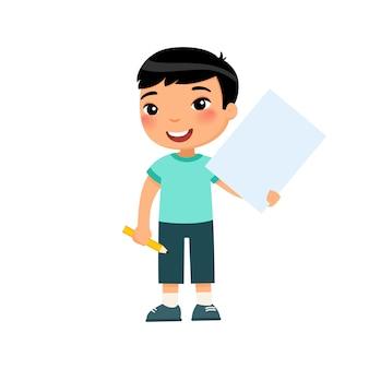 Pequeño muchacho sonriente que celebra el ejemplo plano de la hoja de papel vacía. lindo alumno con cartel en blanco y lápiz en manos aisladas sobre fondo blanco. niño asiático con página de bloc de notas de maquetas