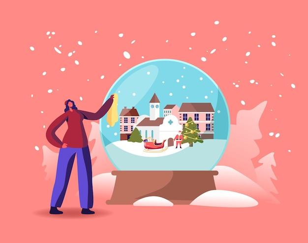 Pequeño personaje femenino con enorme globo de cristal con casas nevadas, iglesia, santa claus, abeto y trineo en el interior