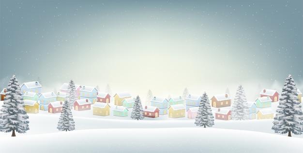 Pequeño pueblo en el fondo de la colina de invierno de nieve