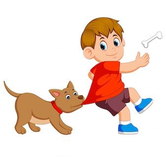 Un perro lindo está golpeando la ropa de su dueño para tomar el hueso.