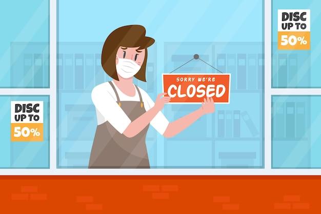 Persona colgando un letrero cerrado debido a la cuarentena por coronavirus
