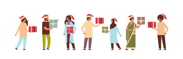 Personas con caja de regalo presentes entre sí feliz navidad feliz año nuevo concepto de celebración de vacaciones personajes de dibujos animados de cuerpo entero