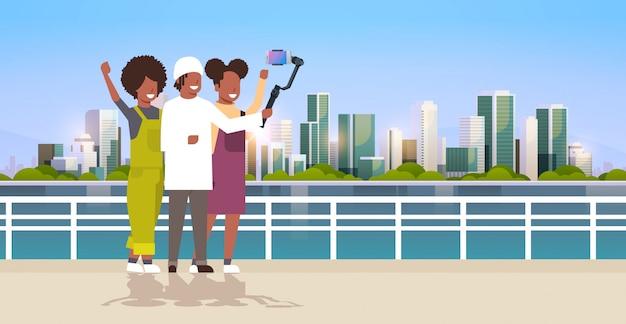 Personas casuales que usan un estabilizador de cardán de 3 ejes selfie stick para teléfonos inteligentes turistas felices tomando fotos de pie juntos sobre el paisaje urbano de fondo horizontal de longitud completa