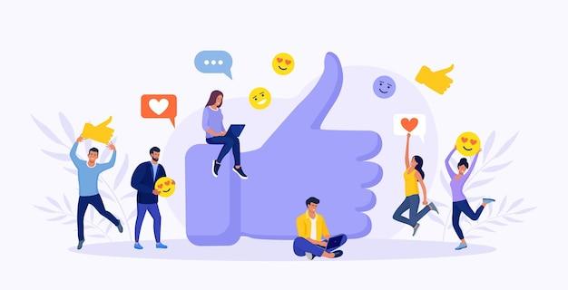 Personas con iconos de redes sociales de pie alrededor de big thumb up. los seguidores masculinos y femeninos dan gustos y comentarios positivos. calificación de revisión del cliente. marketing de internet, smm en los negocios