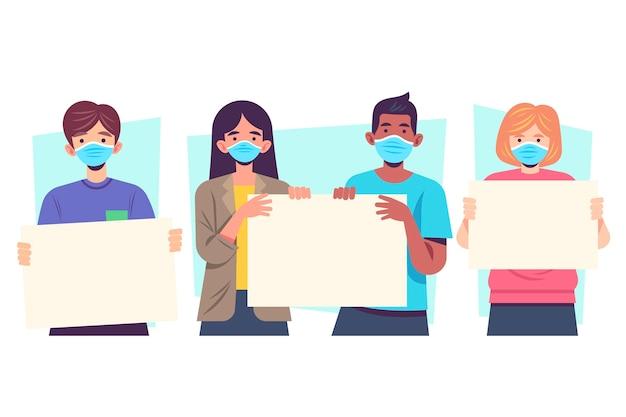 Personas con máscaras médicas con carteles ilustrados.