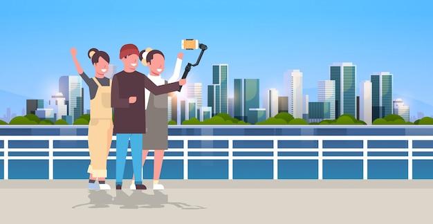 Personas ocasionales que usan el estabilizador de cardán selfie stick para teléfonos inteligentes turistas felices tomando fotos de pie juntos sobre el paisaje urbano de fondo horizontal de longitud completa