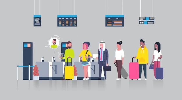 Personas de pie en la cola con maletas para facturar en el aeropuerto pasando por el escáner de seguridad para registrarse