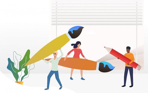 Personas de pie y sosteniendo grandes pinceles y lápices