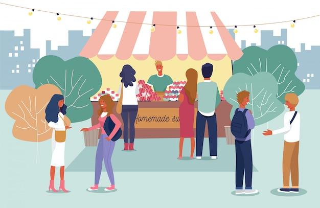 Personas que compran productos caseros en el mercado al aire libre