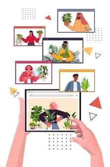Las personas que cuidan de las plantas de interior mezclan amas de llaves de raza discutiendo durante la videollamada en el navegador web vertical vertical de windows