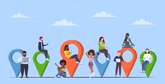 Las personas que usan aparatos digitales punteros geoetiquetas de colores mezclan hombres mujeres cerca de marcadores de ubicación concepto de navegación gps horizontal completo