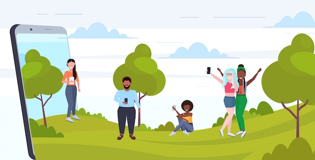 Las personas que usan teléfonos celulares mezclan hombres mujeres caminando al aire libre divirtiéndose concepto de adicción a la tecnología digital pantalla del teléfono inteligente aplicación móvil de longitud completa horizontal